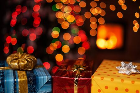 Photo pour Beautiful christmas presents on dark background with blurry xmas tree and fireplace - the calm blessing of holidays - image libre de droit