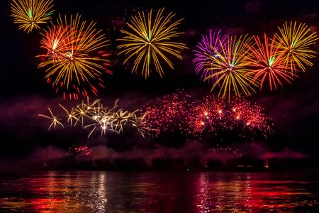 Photo pour Bright festive fireworks reflected in the river - image libre de droit