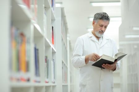 Foto de Renowned scientist/doctor in a library of research center/hospital - browsing a book - Imagen libre de derechos