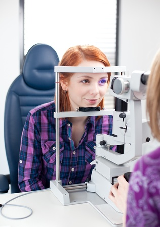 Photo pour optometry concept - pretty young woman having her eyes examined by an eye doctor - image libre de droit