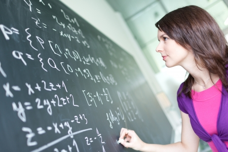 Photo for pretty young college student writing on the chalkboard/blackboard during a math class - Royalty Free Image