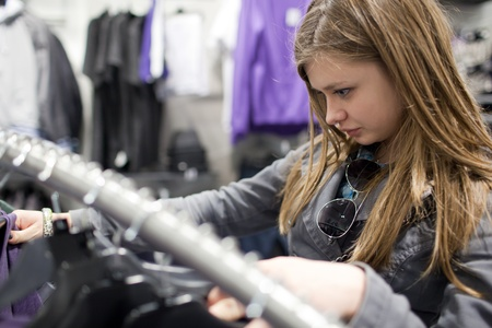 pretty teenager shopping for clothes in a boutique/fashion shop/store (shallow DOF; color toned image)q