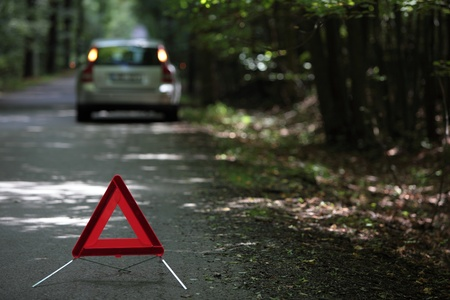 broken down car with warning triangle behind it waiting for assistance to arrive (shallow depth of field, the focus is on the triangle, the car is left out of focus)
