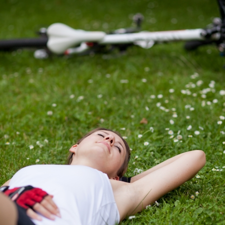 pretty female biker having a rest while on a biking trip