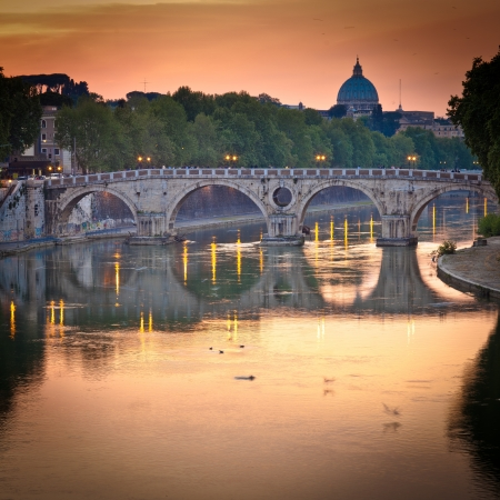 view of st. peter's basilica and the river tiber at sunset - rome, italy