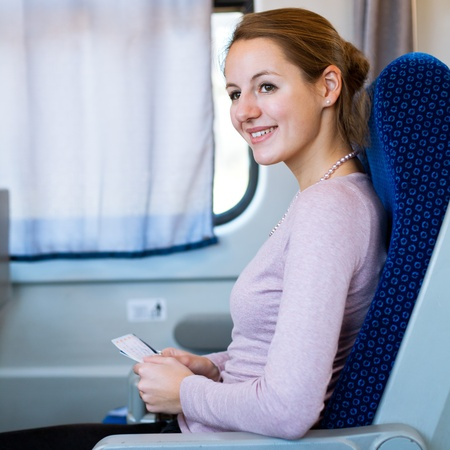 Young woman traveling by train, holding her train ticket , smiling