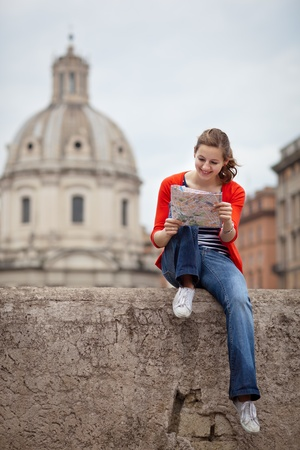Pretty young female tourist studying a map at the Trajan