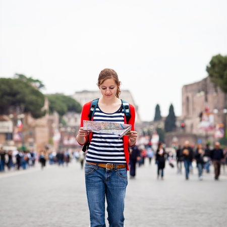 Pretty young female tourist holding a map while walking along the Via del Fori Imperiali avenue in Rome, Italy  with Colosseum in the background