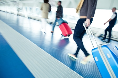 Airport rush  people with their suitcases walking along a corridor  motion blurred image; color toned image
