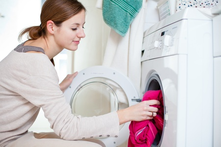 Housework: young woman doing laundry (shallow DOF; color toned image)の写真素材