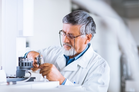 senior male researcher carrying out scientific research in a lab using a gas chromatograph  shallow DOF; color toned image