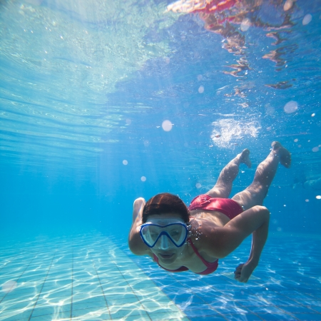 Photo pour Underwater swimming: young woman swimming underwater in a pool, wearing a diving mask - image libre de droit