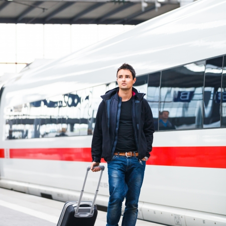 Just arrived  handsome young man walking along a platform at a modern train station