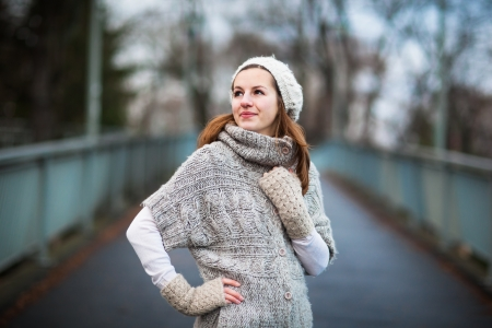 Autumn/winter portrait: young woman dressed in a warm woolen cardigan posing outside in a city park