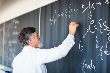 Senior chemistry professor writing on the board while having a chalk and blackboard lecture