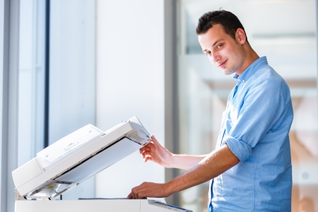 Handsome  young man using a copy machine (shallow DOF; color toned image)