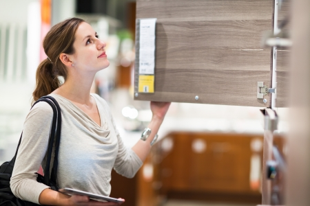 Young woman shopping for furniture in a furniture store, using her tablet computer to compare prices/check for dimensions