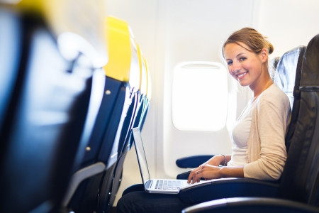 Photo pour Young woman working on her laptop computer on board of an airplane during the flight - image libre de droit