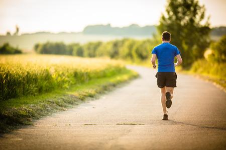 Foto de Male athlete/runner running on road - jog workout well-being concept - Imagen libre de derechos