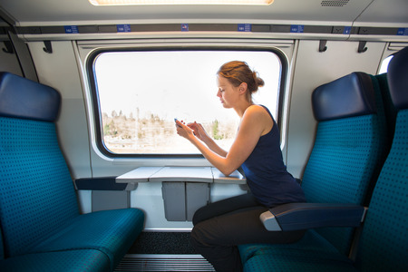 Young woman traveling by train, using her smartphone while sitting on board, alone