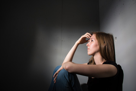 Young woman suffering from a severe depression (very harsh lighting is used on this shot to underline/convey the gloomy mood of the scene)