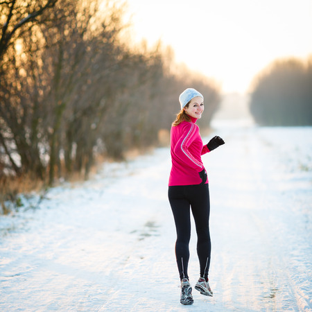 Winter running - Young woman running outdoors on a cold winter dayの写真素材