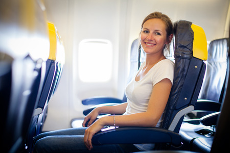 Pretty, young female passenger on board of an aircraft while on the flight
