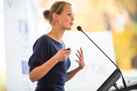 Photo pour Pretty, young business woman giving a presentation in a conference/meeting setting (shallow DOF; color toned image) - image libre de droit