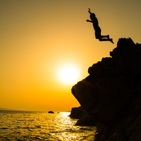 Boy jumping to the sea. Silhouette shot against the sunset sky. Boy jumping off a cliff into the ocean. Summer fun lifestyle.