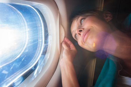 Photo pour Happy, female airplane passanger enjoying the view from the cabon window over the blue sky (shallow DOF; intentional flare) - image libre de droit