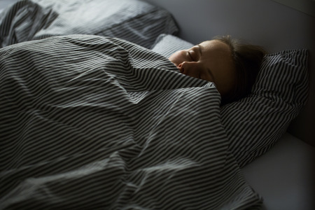 Photo pour Beautiful young woman sleeping in bed - image libre de droit