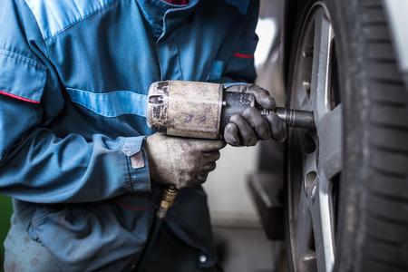 Photo pour mechanic changing a wheel of a modern car (color toned image) - image libre de droit