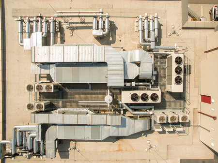 Photo pour Air conditioning equipment atop a modern building - aerial/drone view of the roof with all the necessary installations - image libre de droit