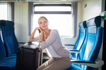 Pretty young woman traveling on a train with her big trunk (color toned image)