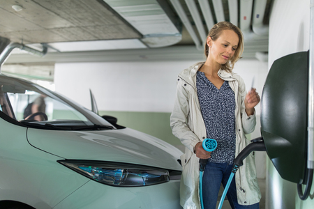 Photo pour Young woman charging an electric vehicle in an underground garage equiped with e-car charger. Car sharing concept. - image libre de droit