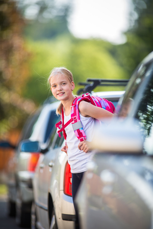 Photo for Cute little girl going home from school, looking well before crossing the street, trying not to get git by a car - Royalty Free Image