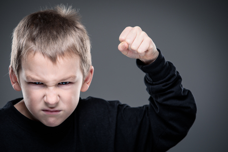 Foto de Loads of aggression in a little boy - education concept hinting behavioral problems in young children (shallow DOF) - little boy with hands clenched into fists about to punch someone - Imagen libre de derechos