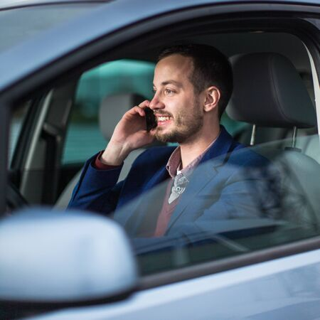 Photo for Handsome young man looking at his cellphone while at the wheel of his car, smiling - Royalty Free Image
