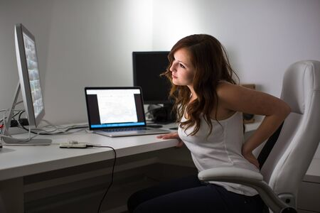 Photo for Woman working on a computer in a home office - suffering form lower back pain - Royalty Free Image