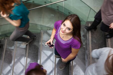 Photo pour At the university/college - Students rushing up and down a busy stairway - confident pretty young female student looking upwards while listening to music on her mp3 player (color toned image) - image libre de droit