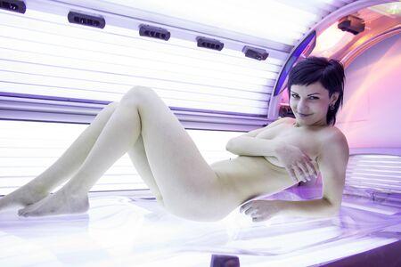 Photo pour Pretty young woman tanning her skin in a modern solarium - image libre de droit