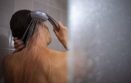 Photo pour Pretty, young woman taking a long hot shower washing her hair in a modern design bathroom - image libre de droit