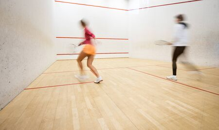 Photo for Two female squash players in action on a squash court (motion blurred image; color toned image) - Royalty Free Image
