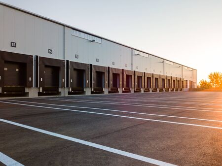 Photo pour Warehouse exterior with loading ramps and slots for trucks to park - modern industry warehouse storage building. - image libre de droit