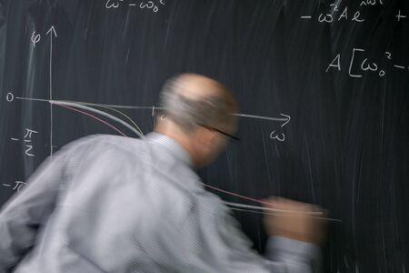 Photo pour Math teacher drawing   fuction graph on a blackboard during mathclass (motion blurred image) - image libre de droit