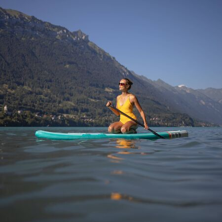 Photo pour Pretty, young woman paddling on a paddle board on a lake, enjoying a lovely summer day - image libre de droit