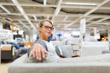Photo pour Pretty, young woman choosing the right furniture for her apartment in a modern home furnishings store (color toned image; shallow DOF) - image libre de droit