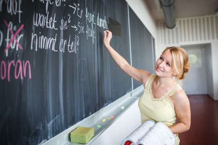 Foto de Pretty young teacher writing on the chalkboard/blackboard during class (shallow DOF; color toned image) - Imagen libre de derechos