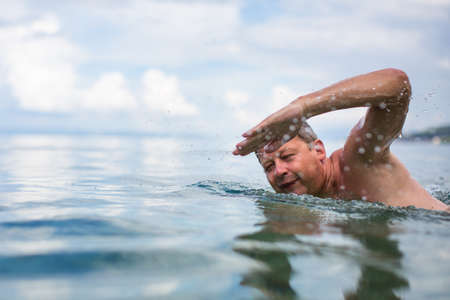Photo pour Senior man swimming in the Sea/Ocean - enjoying active retirement, having fun, taking care of himself, staying fit - image libre de droit