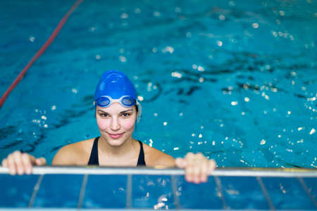 Photo pour Female swimmer in an indoor swimming pool - looking at the camera, smiling wholeheartedly (shallow DOF; color toned image)(shallow DOF) - image libre de droit